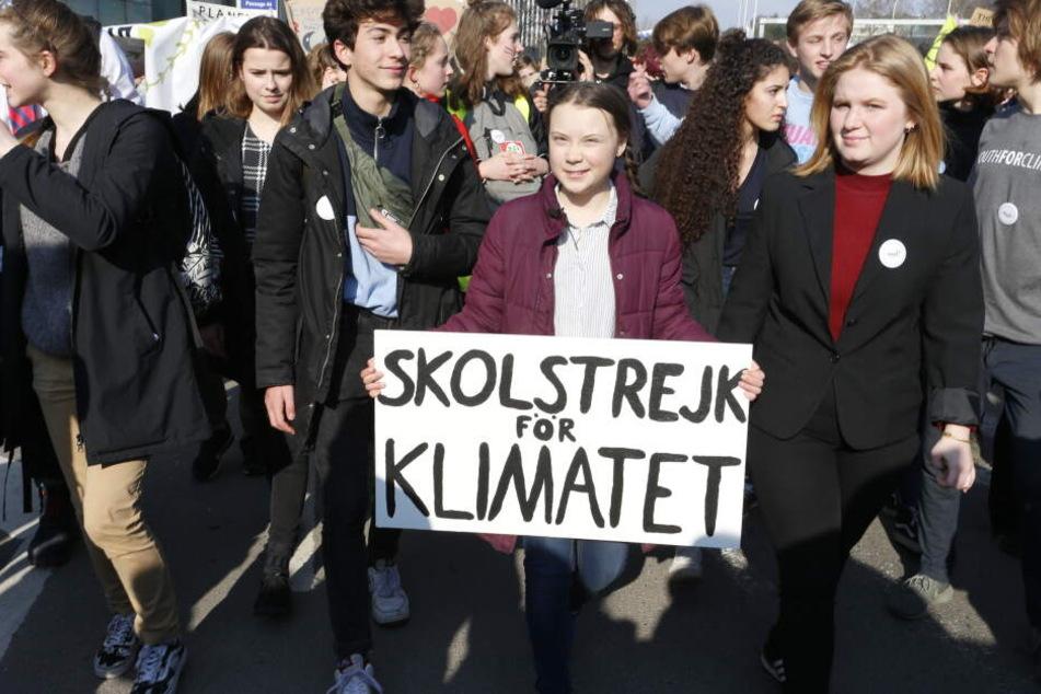 Die Klimaaktivistin Greta Thunberg hält ein Protestschild für Klimaschutz in den Händen.
