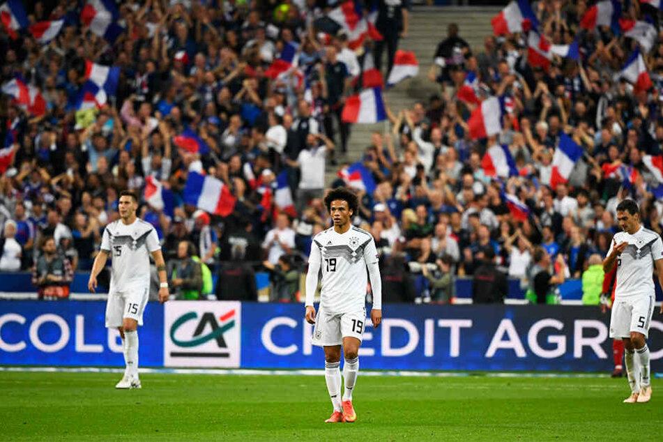 Krasser Kontrast: Die deutschen Spieler um Mats Hummels (r.), Leroy Sané (M.) und Niklas Süle (l.) gucken betreten in die Gegend, während die französischen Fans ein Tor ihrer Mannschaft bejubeln.