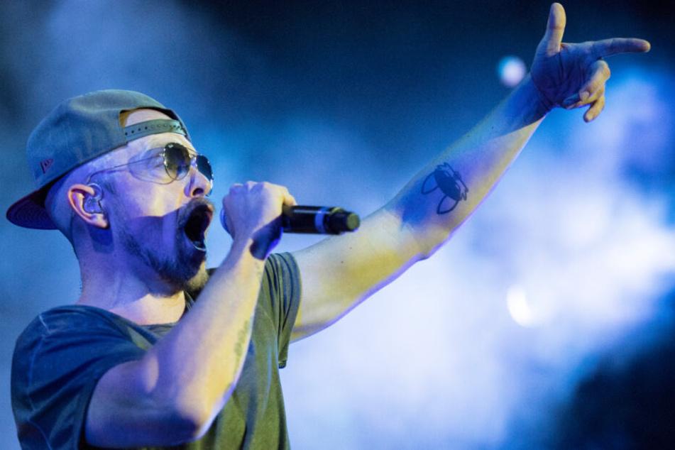So kennt man ihn: Jan Delay mit Cap und Sonnenbrille bei einem Konzertauftritt.