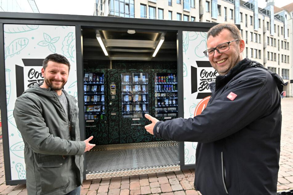 """Roland Keilholz (47, r.) vom """"alexxanders"""" steht mit Ideengeber Daniel Weidener (38) von der Agentur """"Revolte"""" vor einem """"Cook in the Boxx""""-Automaten."""