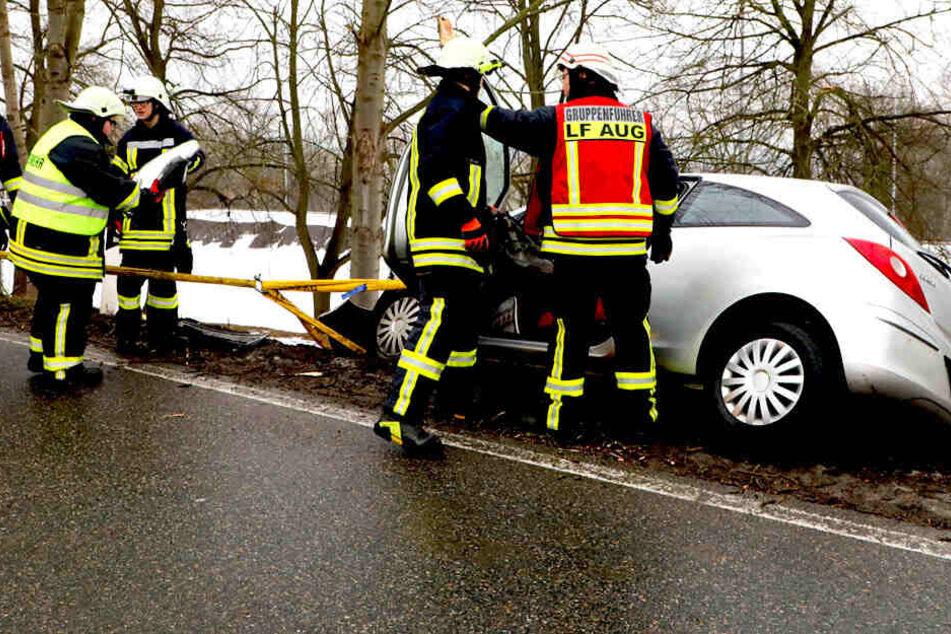 Einsatzkräfte müssen sich um das Auto kümmern, das einen Hang hinunter zu rutschen droht.