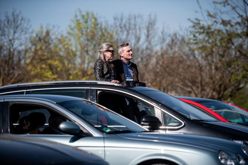 Oberbürgermeister Thomas Geisel sitzt mit seiner Frau Vera in seinem Auto und guckt aus dem Dachfenster Richtung Bühne.