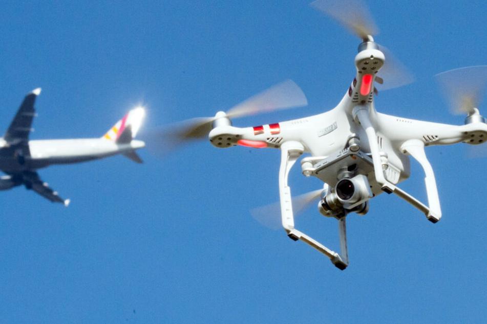 Eine Drohne fliegt in der Nähe eines Flugzeugs. (Symbolbild)