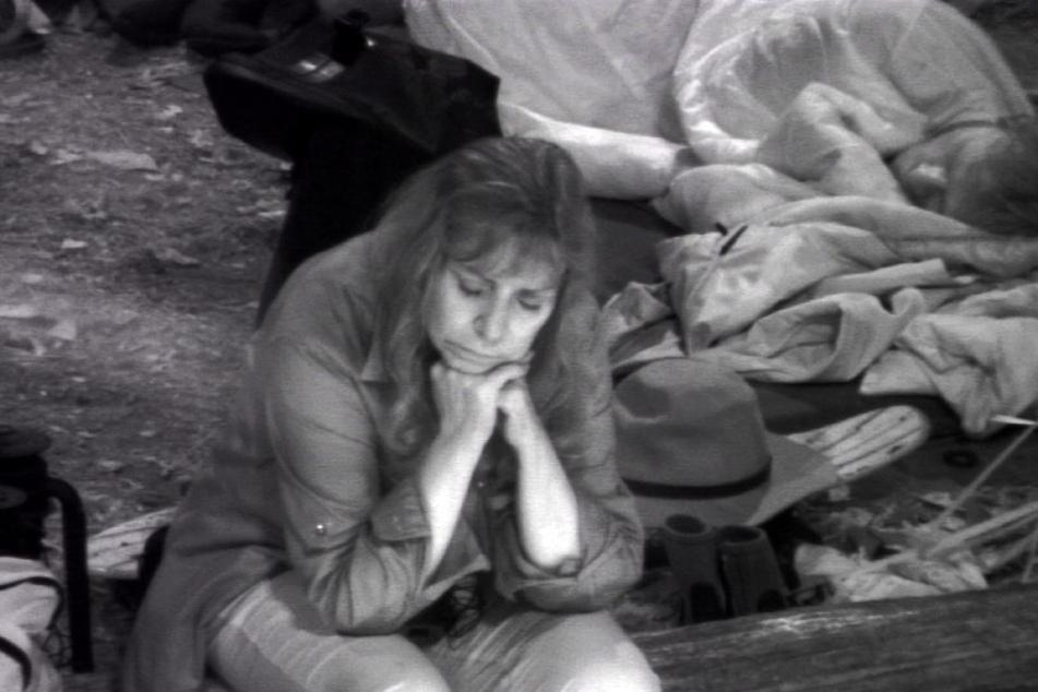 Tina York sitzt wieder allein am Lagerfeuer. Hinter ihr schläft (noch) Ansgar Brinkmann.  Für die Solo-Wache gibt's wieder eine Strafe!