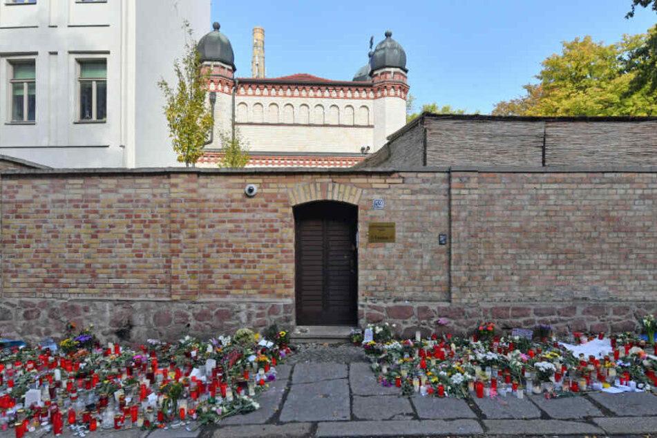 Blumen und Kerzen liegen nach dem rechtsextremen Anschlag neben der Tür zur Synagoge in Halle.