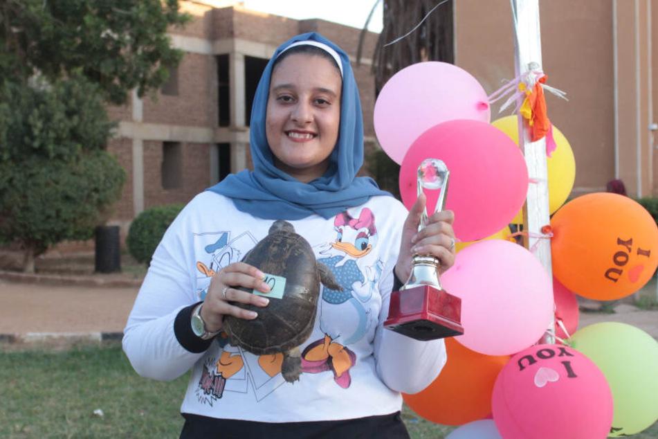 """Dina Rida (hier mit Schildkröte """"Dargot"""" in der Hand) war die strahlende Siegerin eines Schildkrötenrennens in der sudanesischen Hauptstadt Khartum."""