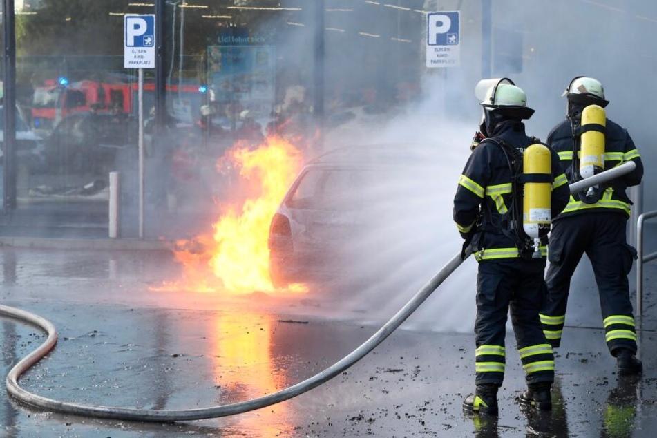 Einsatzkräfte löschen das brennende Fahrzeug.