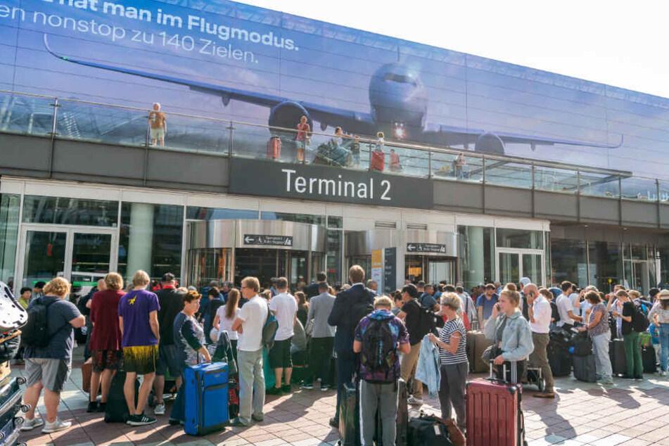 Fluggäste stehen vor dem verschlossenen Eingang zum Terminal 2 am Münchner Flughafen im Außenbereich.