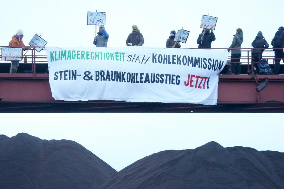 Mit mehreren Plakaten machen die Demonstranten auf sich aufmerksam.