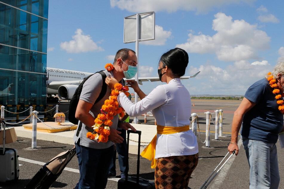 Ein Flughafenbeamter (M) begrüßt einen Passagier bei seiner Ankunft am Flughafen Bali.