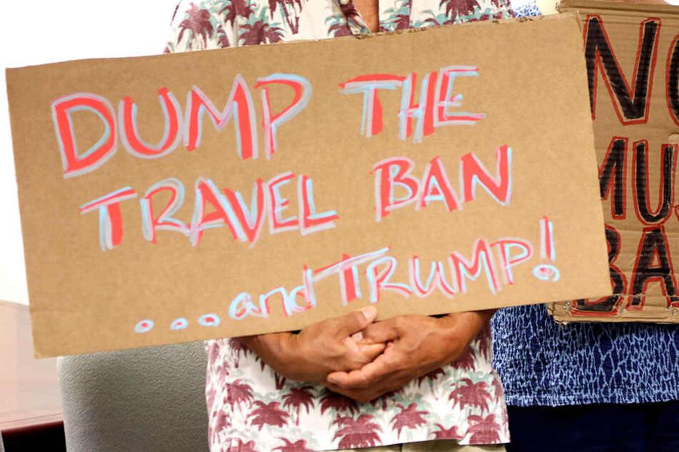 Nicht allen gefällt die strikte Einreisepolitik von Donald Trump. Hier halten Gegner ein Banner hoch.