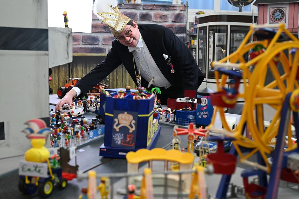 Simon Isser, Sitzungspräsident des Offenbacher Karnevalvereins (OKV), steht in einer Halle in Mühlheim hinter einen nachgebauten Kulisse mit bunten Miniatur-Motivwagen, in denen Playmobilfiguren platziert sind.
