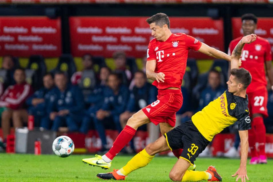Dortmunds Julian Weigl (r) und Bayerns Robert Lewandowski kämpfen um den Ball.