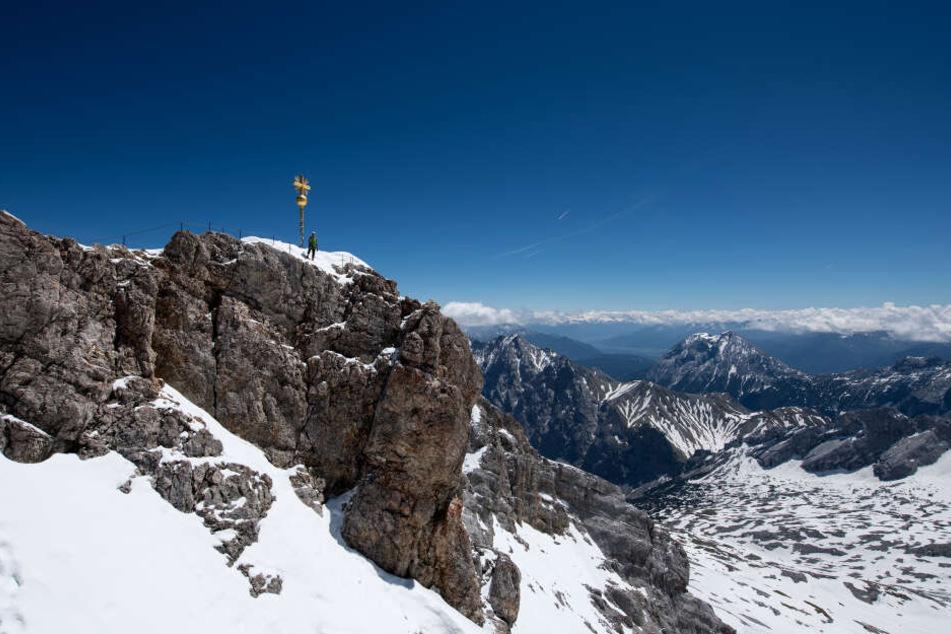 Bayern, Garmisch-Partenkirchen: Ein Bergsteiger nutzt das schöne Wetter, um zum Gipfelkreuz auf der Zugspitze zu klettern.