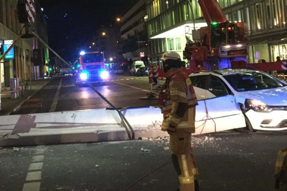 Weil Bus gegen Eckpfeiler fährt: Tonnenschweres Fassadenteil kracht auf Auto