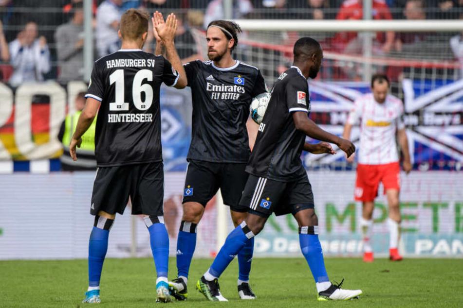 Lukas Hinterseer (von links nach rechts), Martin Harnik und David Kinsombi klatschen nach dem Eigentor von Regensburg zum 1:1 ab.