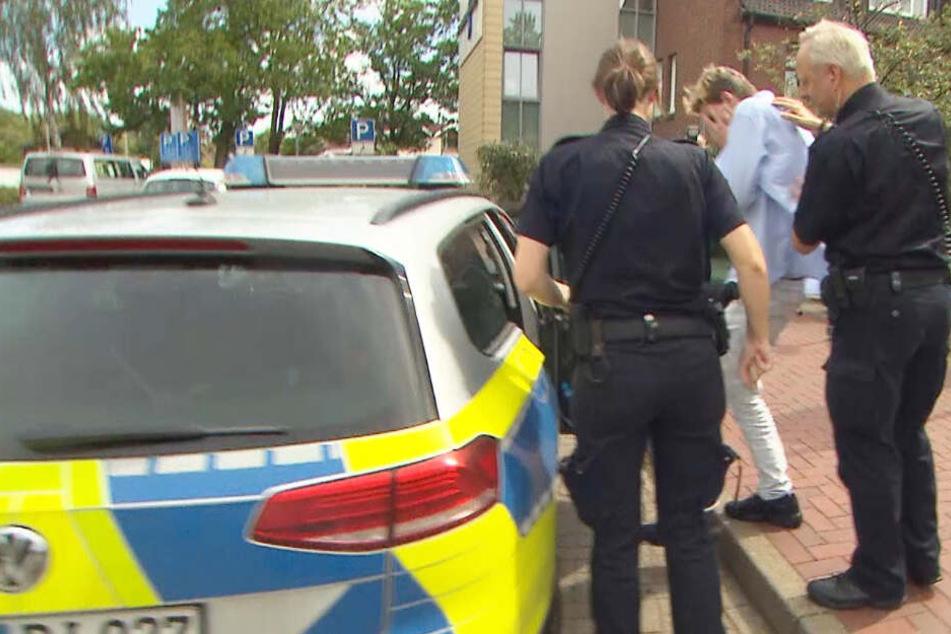 Polizisten führen den Tatverdächtigen ab.