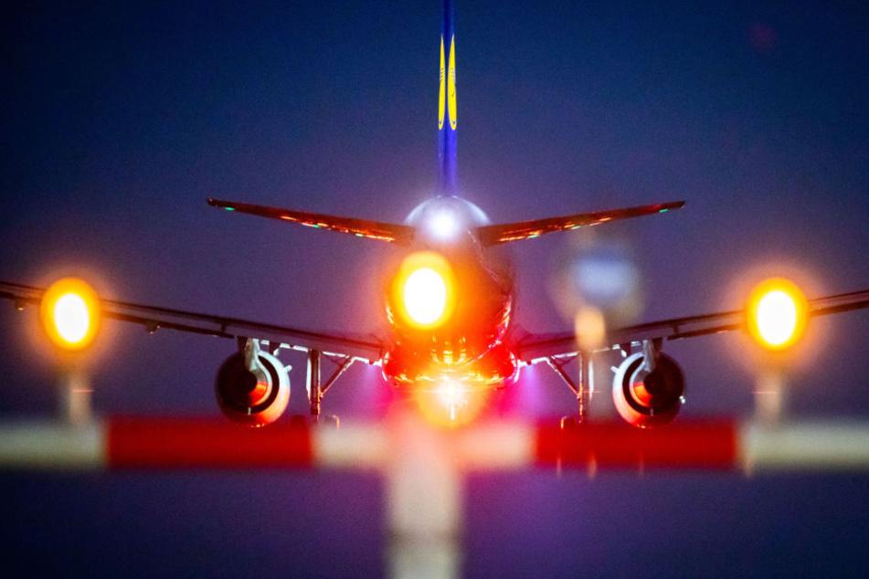 Ein Flieger landet bei Dunkelheit am Frankfurter Flughafen. (Symbolbild)