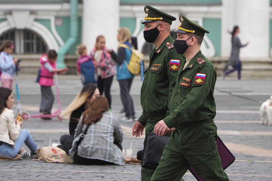 Russland, St.Petersburg: Russische Offiziere tragen Mundschutz und gehen über den Palastplatz, während eine Gruppe junger Menschen im Hintergrund zu sehen ist.
