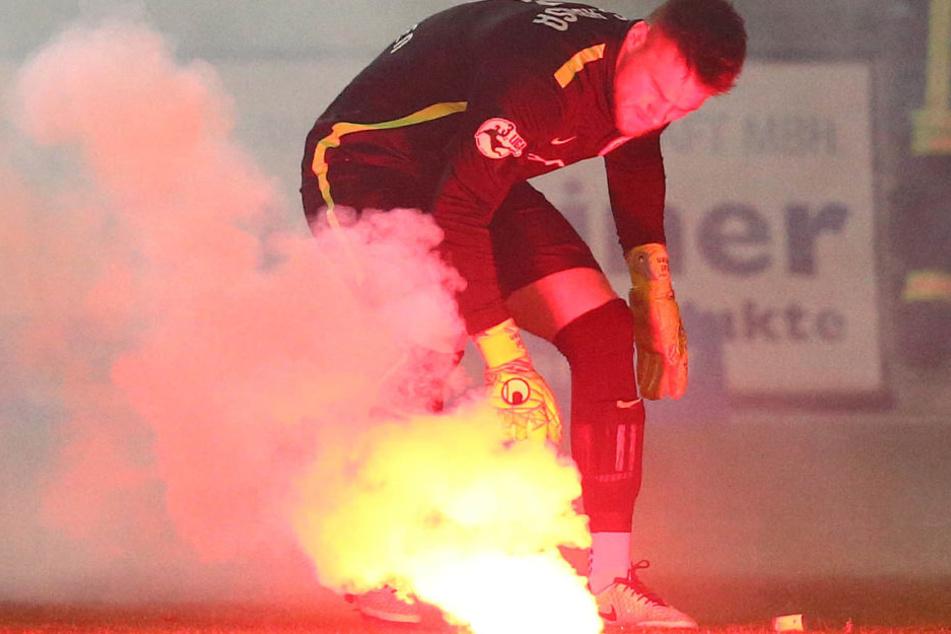 Fans vom FC Hansa Rostock zündeten Bengalische Feuer - Hansa-Keeper Marcel Schuhen versucht, ein brennendes Bengalo vom Rasen zu entsorgen.