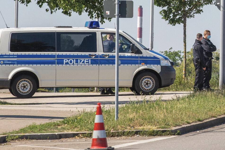 Beamte und ein Einsatzfahrzeug der Bundespolizei stehen nahe einer Brücke am Grenzübergang nach Frankreich. (Archivbild)