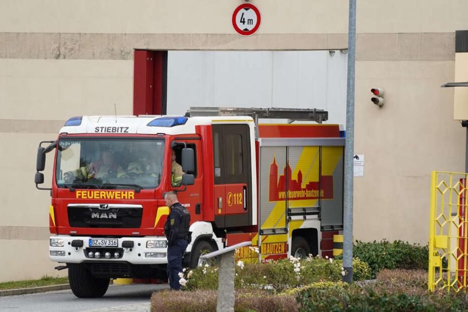 Ein Feuerwehrfahrzeug fährt durch das Tor der JVA Bautzen.