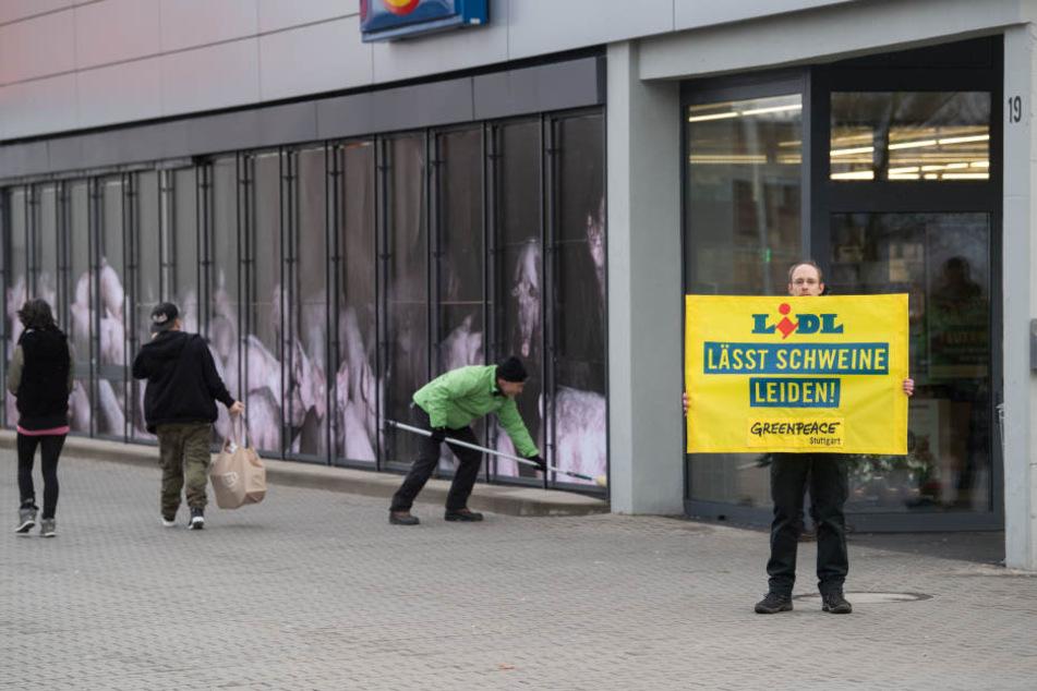 """Ein Greenpeace-Aktivist hält vor einer Lidl-Filiale ein Transparent mit der Aufschrift """"Lidl lässt Schweine leiden! Greenpeace Stuttgart"""" in den Händen."""