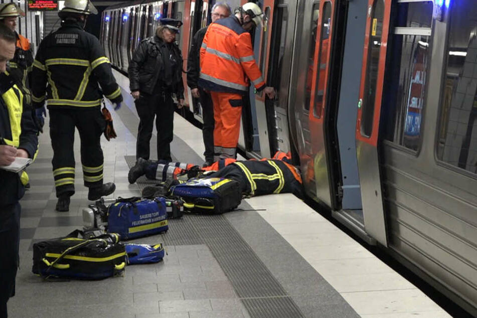 Ein Feuerwehrmann liegt am Boden und spricht mit dem Jugendlichen, der ins Gleisbett gefallen war und sich in einen Zwischenraum retten konnte.