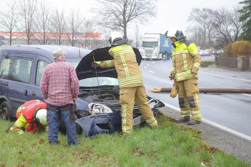 Kameraden der Feuerwehr stehen an dem Unfallauto und prüfen, ob Betriebsstoffe auslaufen.