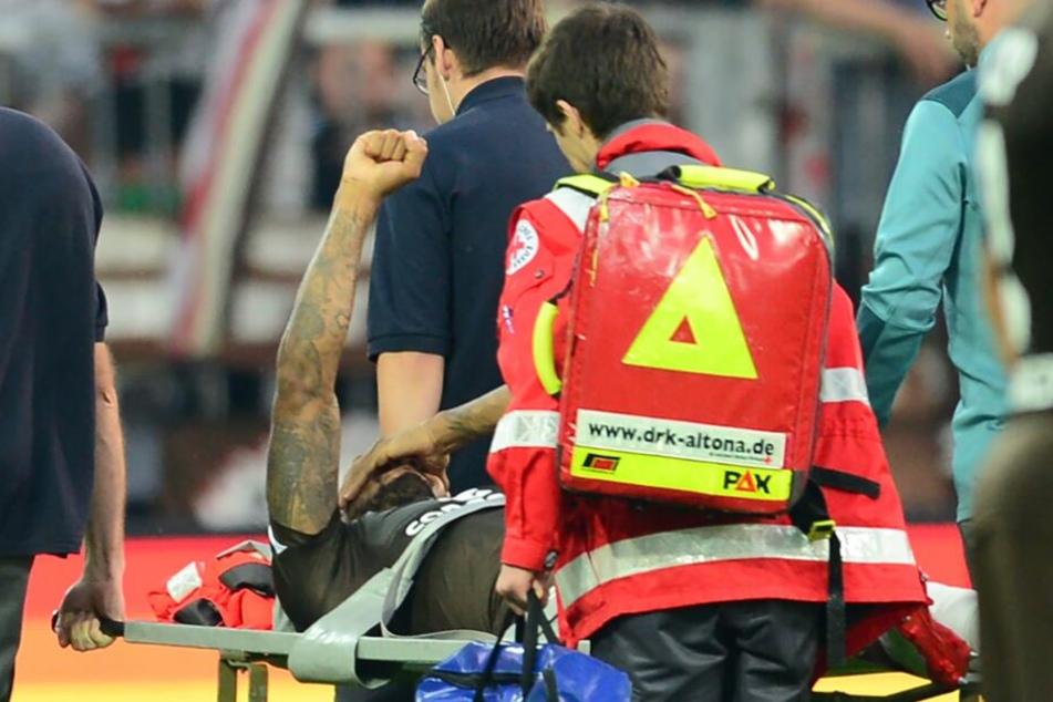 Der schwer Verletzte erhebt eine Faust, als der Gesang der Fans ertönt.