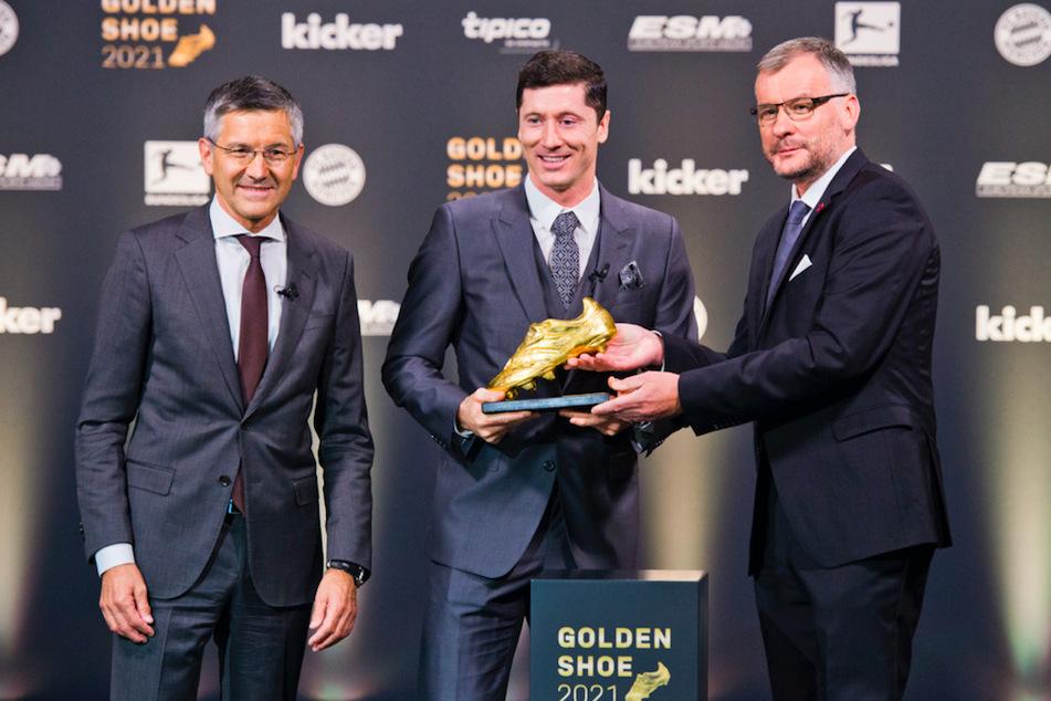 Kicker-Chefredakteur Jörg Jakob (v.r.n.l.) übergibt den Goldenen Schuh 2021 an Fußballprofi Robert Lewandowski (33) vom FC Bayern München neben Herbert Hainer (67), Vorstandsvorsitzender des Vereins.