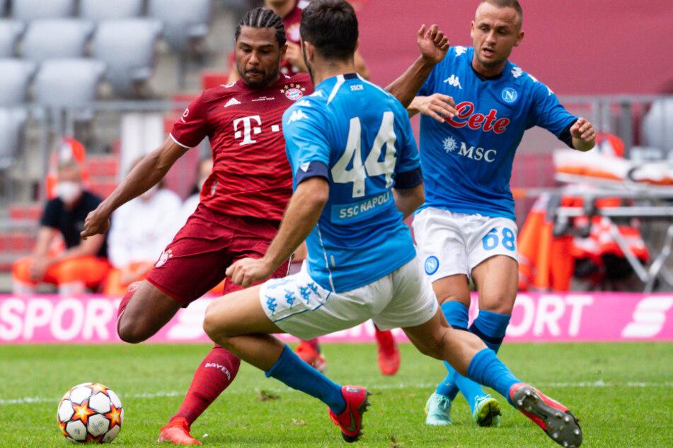 Serge Gnabry (l.) schließt unter Bedrängnis von Kostas Manolas (M) und Stanislav Lobotka ab.