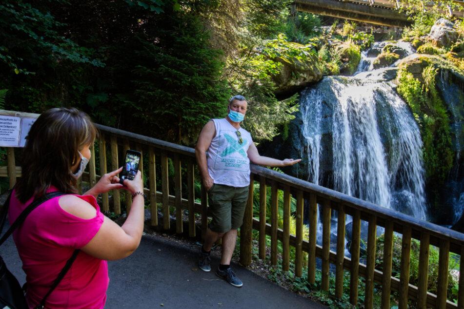 Ein Tourist steht an einem Geländer und posiert für ein Foto, während seine Begleiterin mit ihrem Smartphone ein Bild von ihm vor einer Stufe der Triberger Wasserfälle macht.