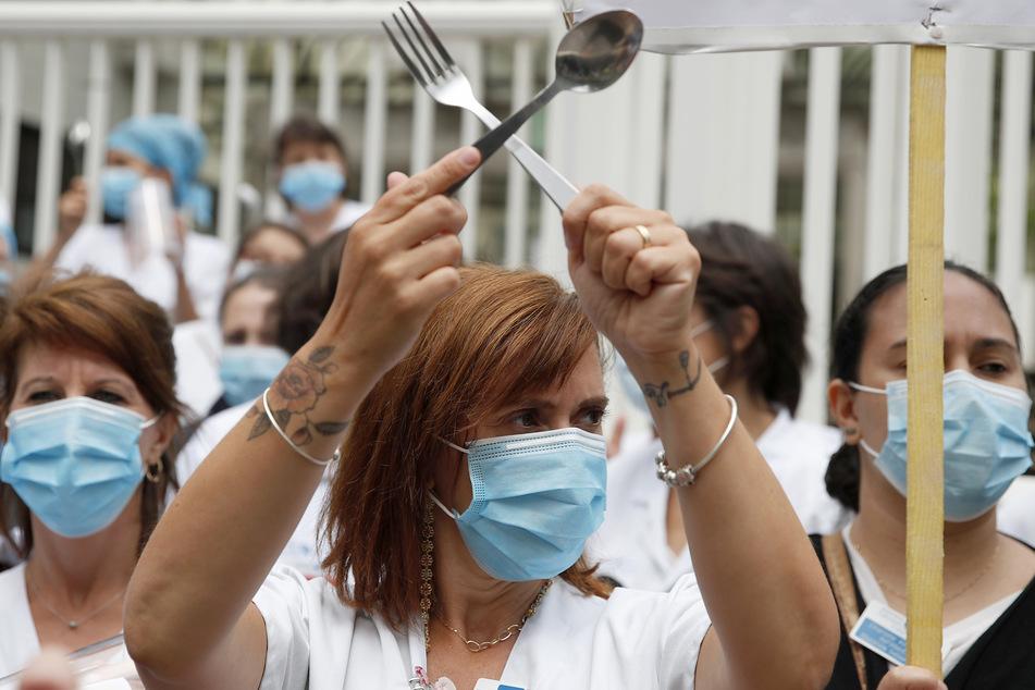 Eine Krankenschwester mit Mundschutz schlägt mit einen Löffel und eine Gabel gegeneinander bei einer Demonstration von medizinischem Personal vor dem Robert Debre Krankenhaus in Paris. Französische Krankenschwestern und Ärzte fordern eine bessere Bezahlung und ein Umdenken in einem einstmals renommierten öffentlichen Gesundheitssystem, das schnell von Zehntausenden von Viruspatienten überfordert war.