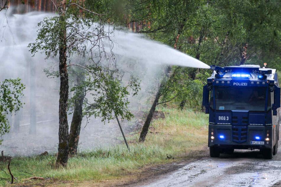 Ein Wasserwerfer der Polizei löscht einzelne Glutnester im Wald bei Lübtheen.