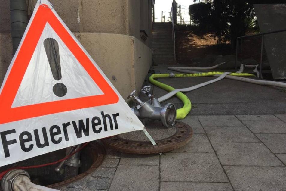 In der Arnulfstraße, wo Feuerwehr und THW den vollgelaufenen S-Bahn-Tunnel auspumpen, steht ein Schild der Feuerwehr neben Schläuchen.
