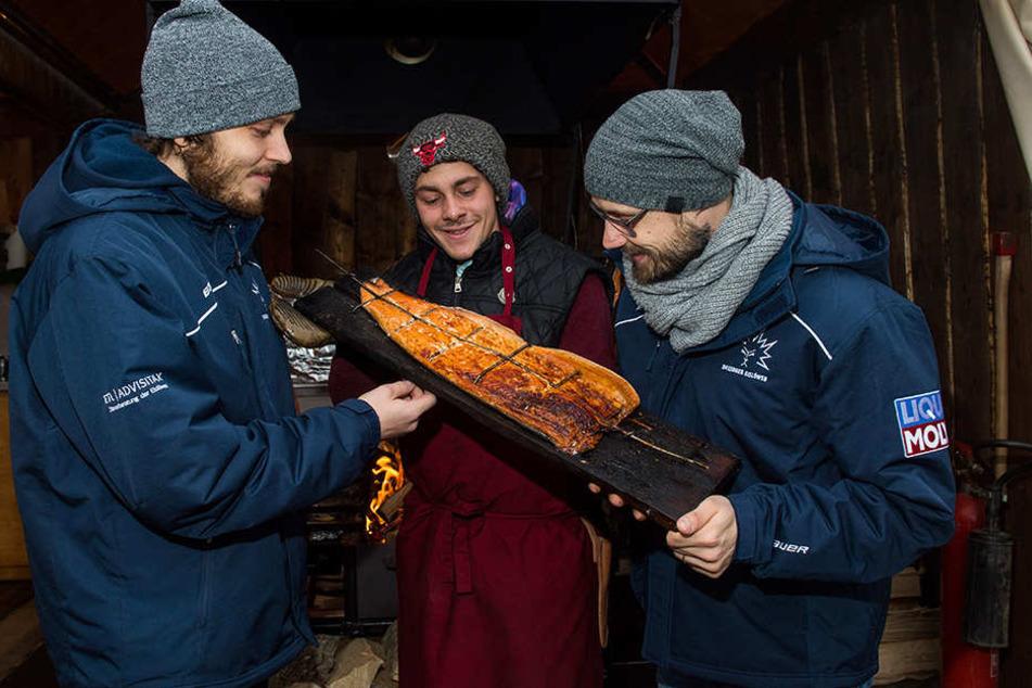 Teemu Rinkinen (l.) und Ville Hamälainen (r.) ließen sich den Lachs von Dominik Lagrin am Goldenen Reiter schmecken.