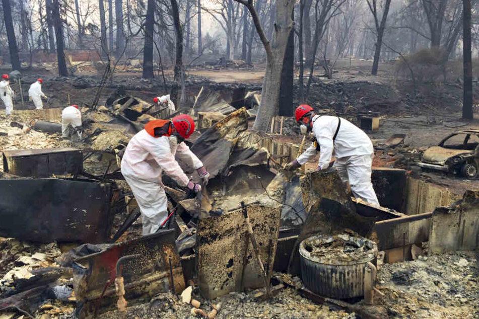 """Freiwillige Rettungskräfte suchen in den Trümmern von Häusern, die dem """"Camp""""-Feuer zum Opfer gefallen sind, nach menschlichen Überresten."""