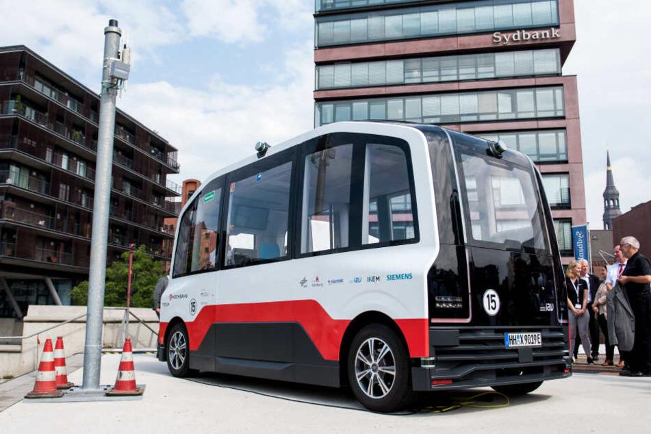 Ein autonom fahrenden Elektro-Kleinbus der Hamburger Hochbahn steht neben einer Datensäule in der HafenCity.