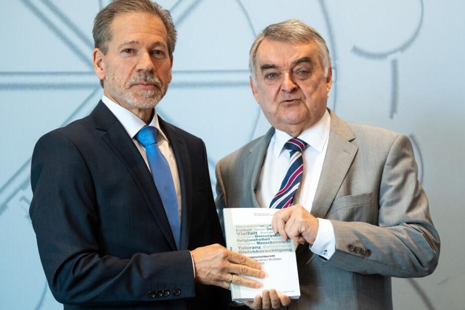 Burkhard Freier (l), Leiter des Verfassungsschutzes NRW, übergibt Herbert Reul (CDU), Innenminister von Nordrhein-Westfalen, den Verfassungsschutzbericht.