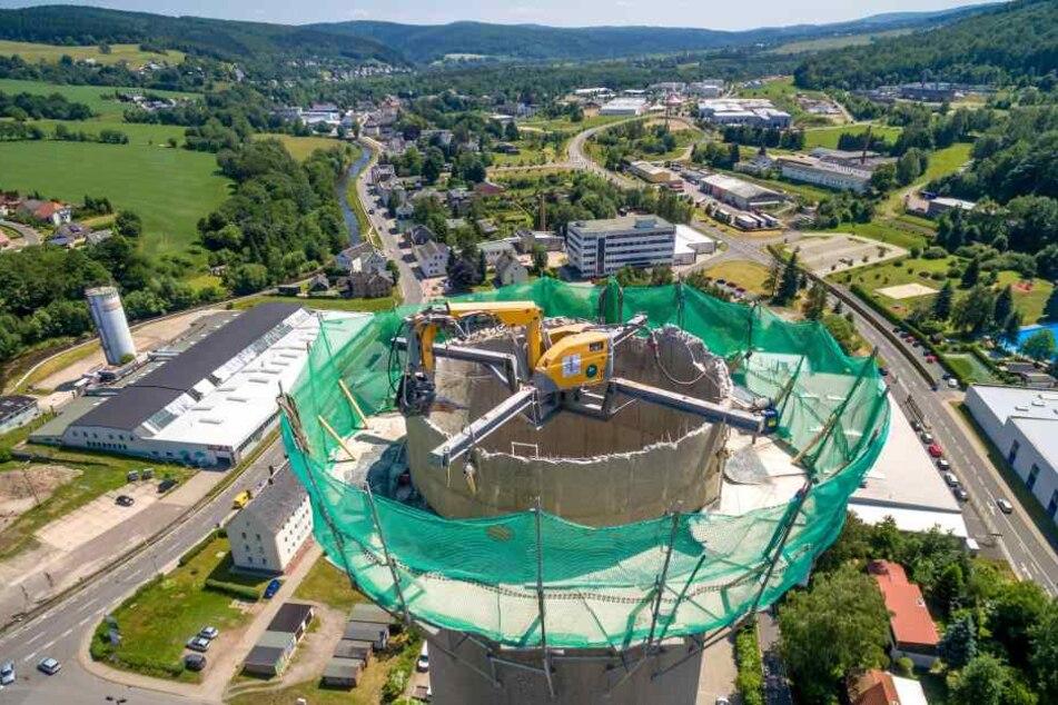 Der Mitte der 1980er Jahre errichtete Schornstein des ehemaligen Heizkraftwerkes in Olbernhau wird derzeit abgerissen. Eine Baggerspinne knabbert sich von oben nach unten.