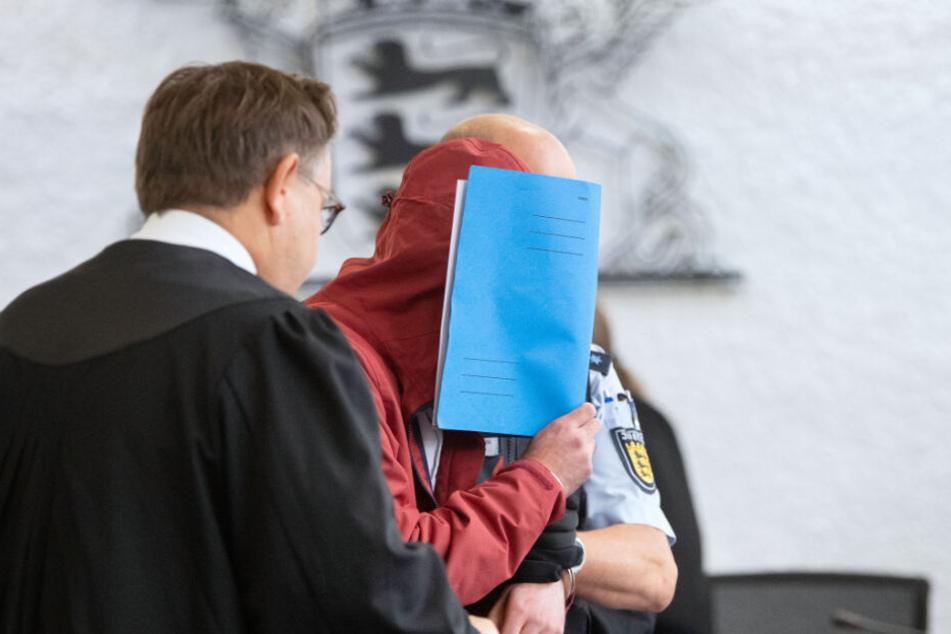Der Angeklagte (M) in einem Mordprozess nach einem tödlichem Unfall wird von einem Justizbeamten in einen Gerichtssaal des Landgerichts Stuttgart geführt.