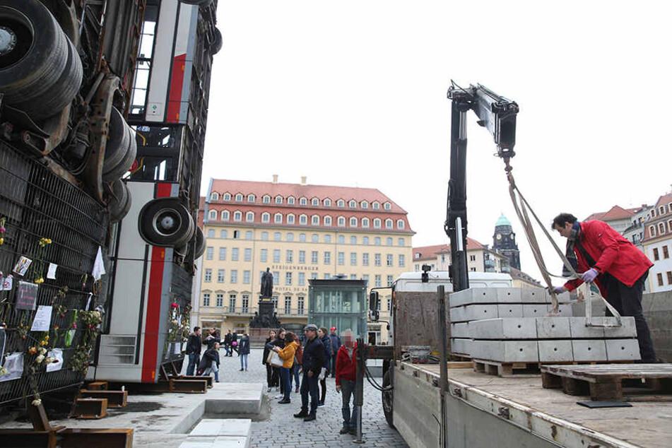 Der Sockel des Bus-Kunstwerks wird mit Beton-Platten beschwert.
