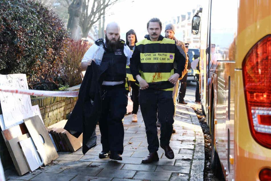 """Ein Polizist führt einen verkleideten Demonstranten von """"Extinction Rebellion"""" ab."""