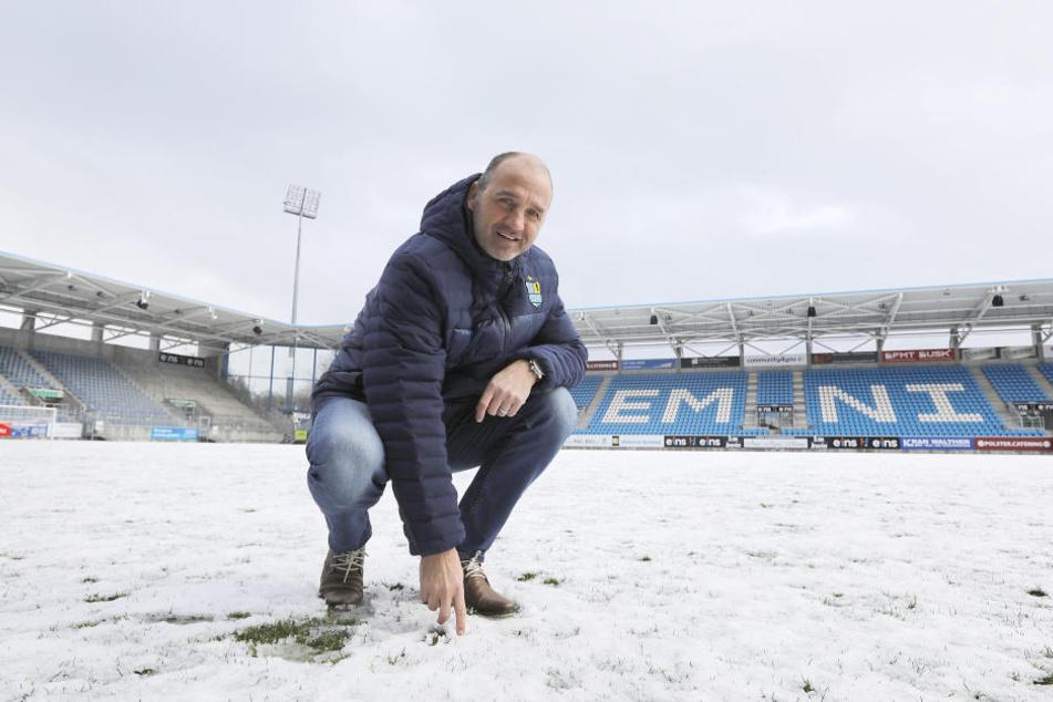 Sportvorstand Steffen Ziffert schaut skeptisch. Das schneebedeckte Spielfeld zeigte sich am Donnerstagmittag in keinem guten Zustand.