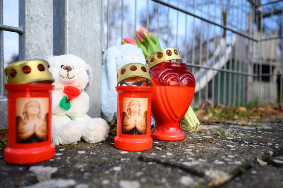 Kerzen, Blumen und Kuscheltiere stehen vor dem Eingang zum Spielplatzgelände.