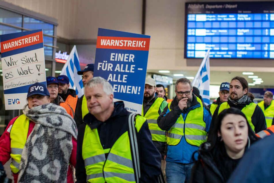 Streikende Mitarbeiter gehen durch den Hauptbahnhof.