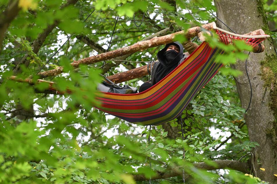 Eine Aktivistin hängt im Maulbacher Wald in einer Hängematte in einem Baum.