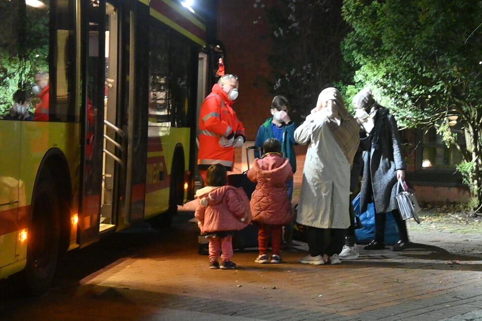 Menschen werden in Bussen zum Quarantäne-Standort gebracht.