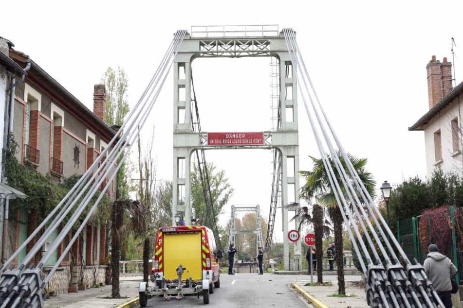 Rettungskräfte stehen vor der abgesperrten Brücke.